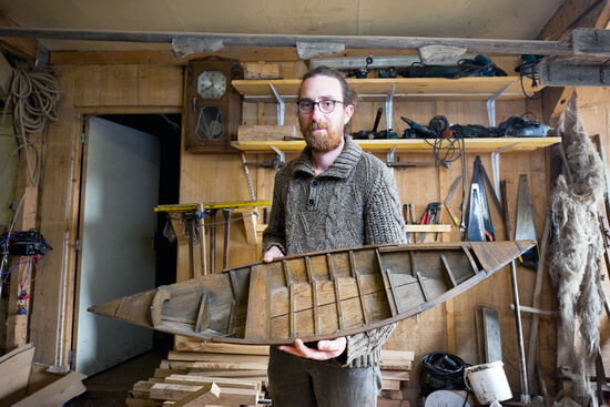 Rémy Colin perpetuates a local boatbuilding tradition in his workshop in Saint-Omer, France. In his hands, Rémy holds a small model of an escute, one of the types of vessels he builds (photo © Rudolf Abraham).