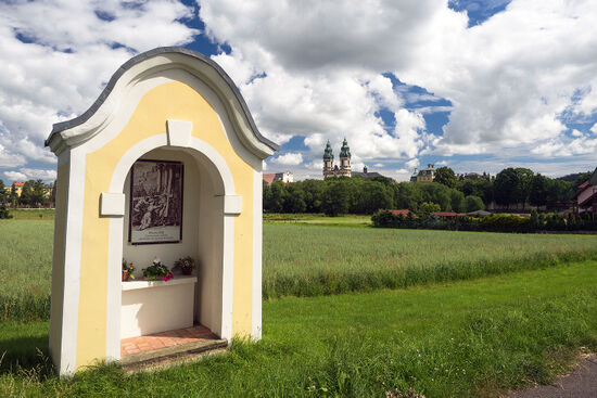 One of the wayside shrines on the pilgrim route of prayer, with the Krzeszów Basilica in the distance (photo © hidden europe).