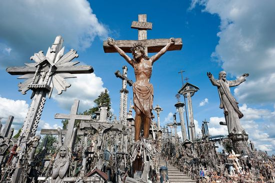 Lithuania's famous Hill of Crosses. The large, roofed wooden cross to the right of the steps (framed here by the two large sculptures of Christ), is by Juozapas Jakstas (photo © Rudolf Abraham).
