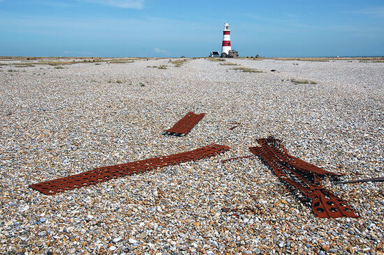 Orford Ness, a shingle spit once used for secret militarypurposes, with military detritus in foreground and OrfordLighthouse in the distance (photo © Laurence Mitchell).