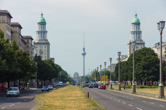 Looking west from Frankfurter Tor along Karl-Marx-Allee, Berlin. The two ceremonial towers were designed by Hermann Henselmann, who also did the initial design concept for the Alexanderplatz TV Tower in the distance (photo © Sergey Kohl /dreamstime.com).