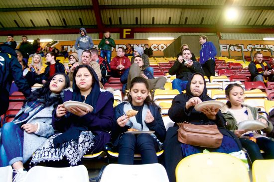 Sustenance at half time, as the Bangla Bantams tuck into samosas on the terraces at Bradford City's Valley Parade Stadium (photo © Emma Levine).