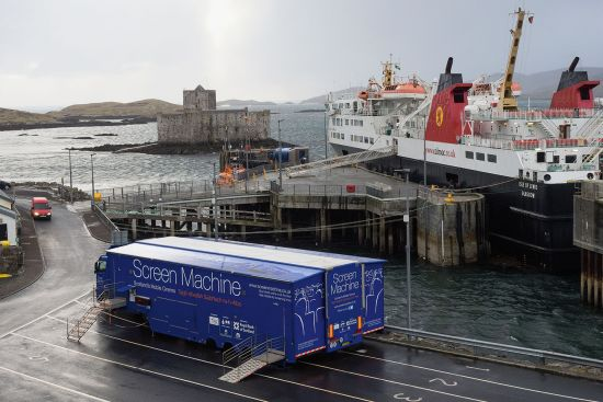 A dreich day in Castlebay on Barra in January 2018,with Kisimul Castle in the bay, the MV 'Isle of Lewis' at the quay and the mobile cinema waiting for the crowds (photo © hidden europe).