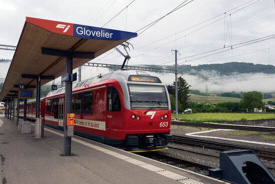 A CFS train to La Chaux-de-Fonds waiting in the bay platform at Glovelier station on a misty summer morning (photo © hidden europe).